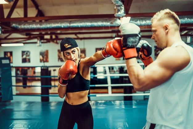 Giovane donna che si esercita con l'istruttore alla lezione di boxe e dell'autodifesa Foto Premium