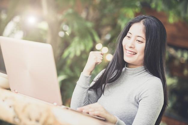 Giovane donna che si siede nella caffetteria al tavolo di legno, bere caffè e usando il portatile. Foto Premium