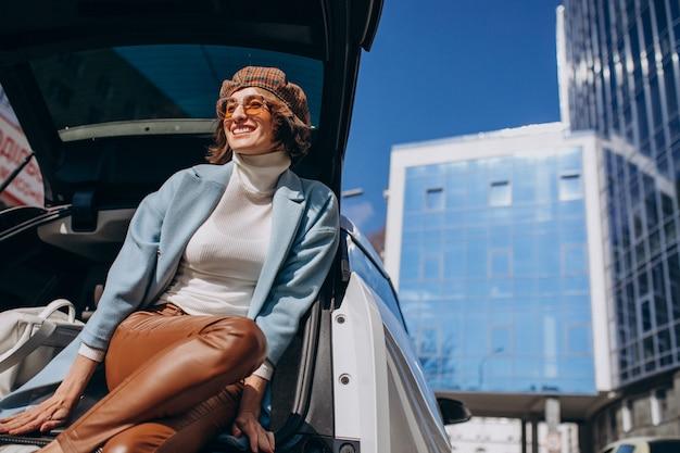 Giovane donna che si siede nella parte posteriore della macchina parlando al telefono Foto Gratuite