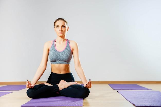 Giovane donna che si siede sul pavimento nella posizione di loto mentre meditating Foto Premium