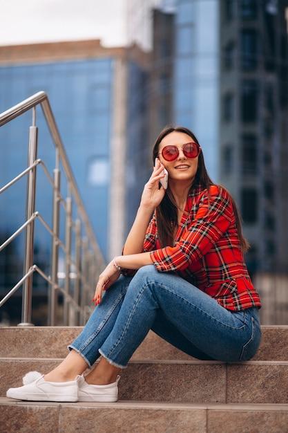 Giovane donna che si siede sulle scale e parlando al telefono Foto Gratuite