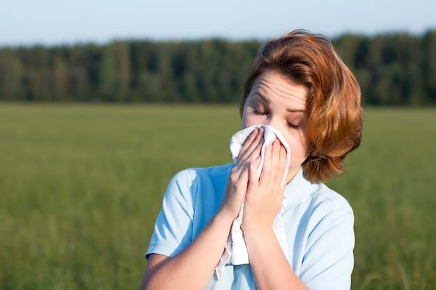 Giovane donna che soffia il naso con il tessuto, moccio in un fazzoletto di carta all'aperto. ragazza malata starnutisce con gli occhi chiusi in un campo estivo. sfondo naturale. sentirsi male, male, male, sofferenza. allergia. Foto Premium