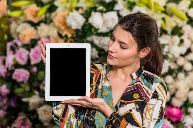 Giovane donna che sta con la compressa in serra Foto Gratuite