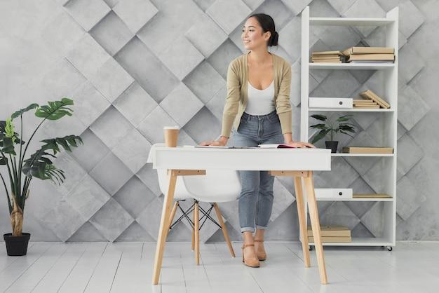Giovane donna che sta nel suo colpo lungo dell'ufficio Foto Gratuite