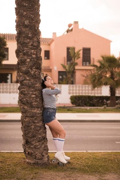 Giovane donna che sta sotto la musica d'ascolto dell'albero sulla cuffia dal bordo della strada Foto Gratuite