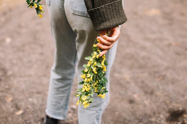 Giovane donna che tiene alcuni fiori selvatici Foto Gratuite
