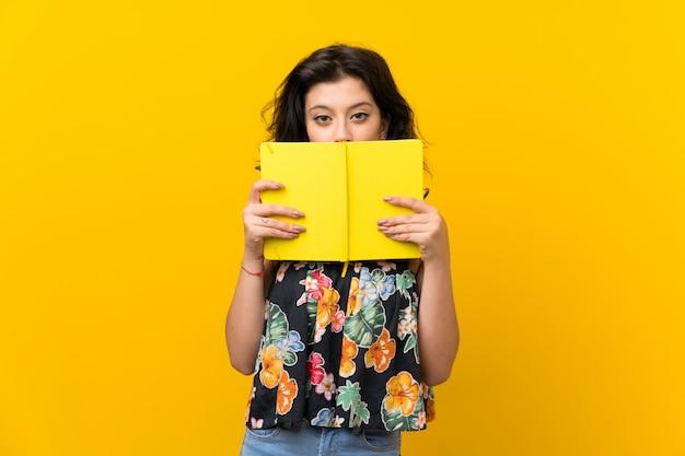 Giovane donna che tiene e che legge un libro Foto Premium