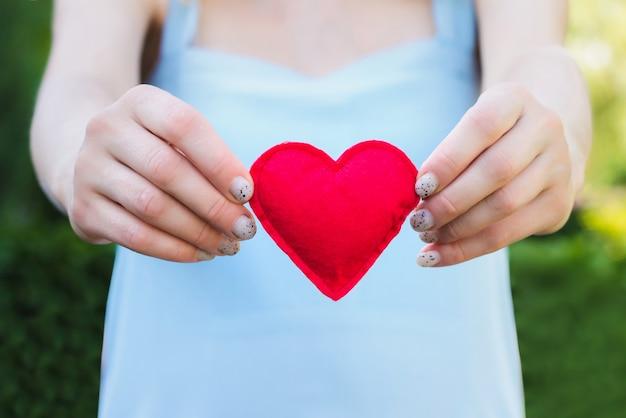 Giovane donna che tiene un cuore rosso nelle sue mani Foto Premium