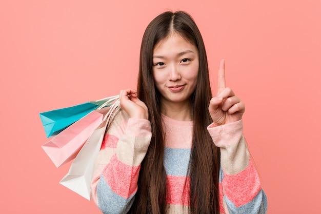 Giovane donna che tiene un sacchetto della spesa che mostra numero uno con il dito. Foto Premium