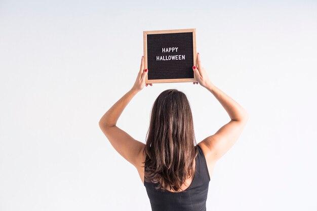 Giovane donna che tiene un tabellone per le affissioni dell'annata nero con il segno felice di halloween. stile di vita al chiuso Foto Premium