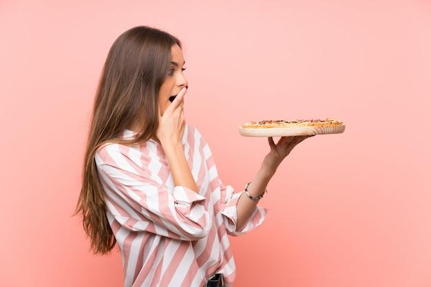Giovane donna che tiene una parete rosa isolata pizza Foto Premium