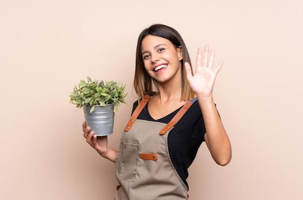 Giovane donna che tiene una pianta che saluta con la mano con l'espressione felice Foto Premium