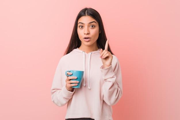 Giovane donna che tiene una tazza che ha una grande idea, concetto di creatività. Foto Premium