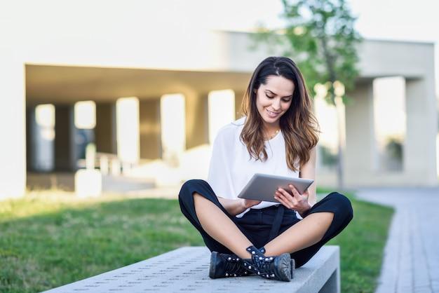 Giovane donna che utilizza compressa digitale che si siede all'aperto nel fondo urbano. Foto Premium