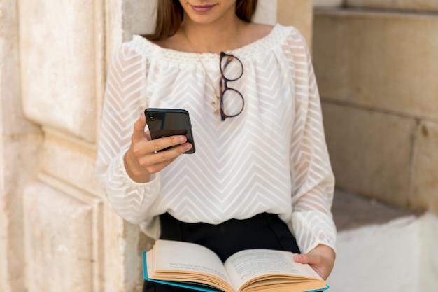 Giovane donna che utilizza il telefono in strada Foto Gratuite