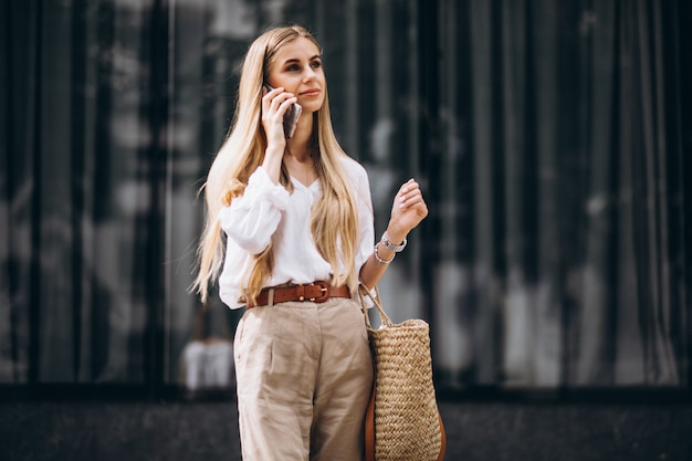 Giovane donna che utilizza telefono fuori nella città Foto Gratuite