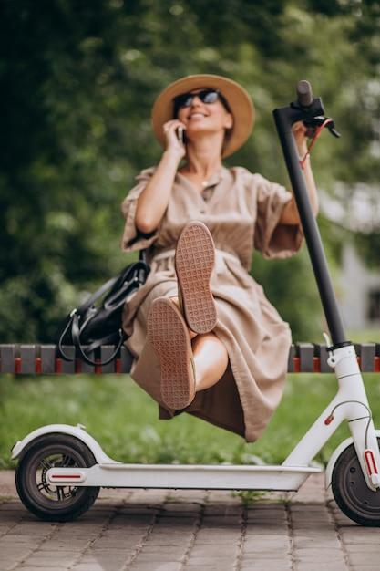 Giovane donna che utilizza telefono nel parco che si siede sul banco dallo scooter Foto Gratuite