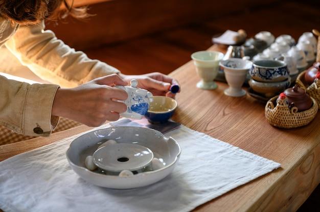 Giovane donna che versa tè caldo in tazza da the Foto Premium