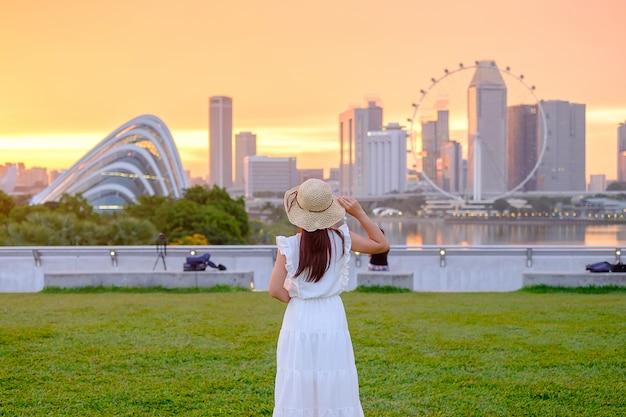 Giovane donna che viaggia con cappello al tramonto, visita asiatica felice del viaggiatore nella città di singapore del centro. punto di riferimento e popolare per le attrazioni turistiche. concetto di viaggio in asia Foto Premium