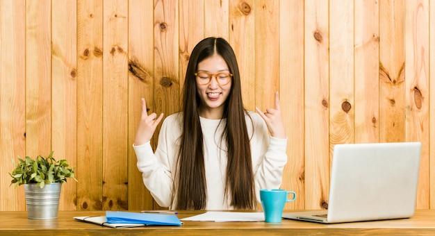 Giovane donna cinese che studia sul suo scrittorio che mostra gesto della roccia con le dita Foto Premium