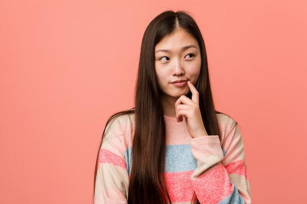 Giovane donna cinese fredda che guarda lateralmente con l'espressione dubbiosa e scettica. Foto Premium