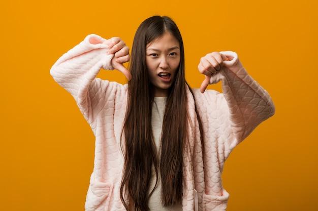 Giovane donna cinese in pigiama che mostra pollice giù e che esprime antipatia. Foto Premium