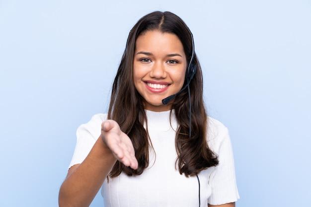 Giovane donna colombiana di telemarketer sopra la stretta di mano isolata della parete blu dopo il buon affare Foto Premium