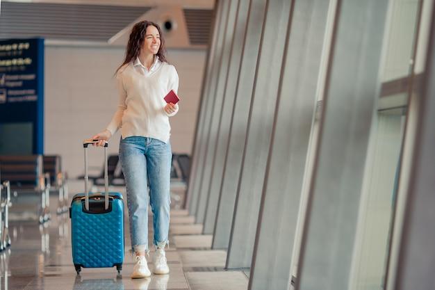 Giovane donna con bagagli in aeroporto internazionale. passeggero di linea aerea in un salotto dell'aeroporto in attesa di volo aereo Foto Premium