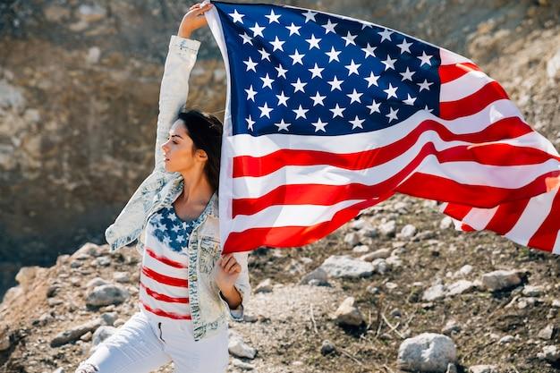 Giovane donna con bandiera americana guardando lontano Foto Gratuite