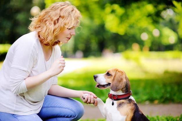 Giovane donna con cane beagle nel parco estivo. animale domestico ubbidiente con il suo padrone che pratica il comando della zampa Foto Premium