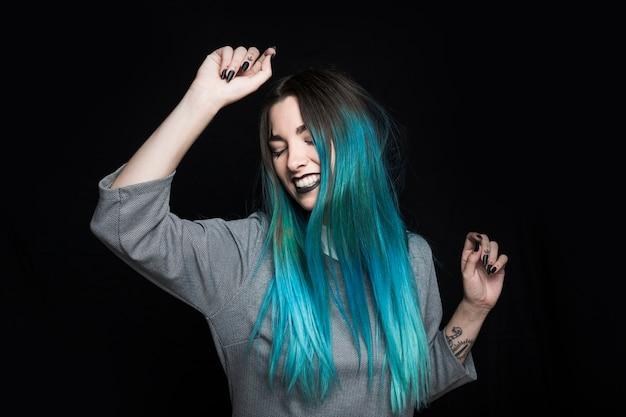 Giovane donna con capelli blu ballando in studio Foto Gratuite