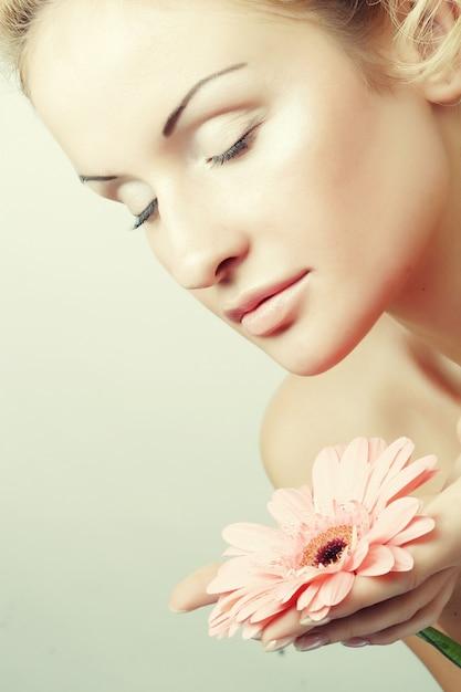 Giovane donna con fiore di gerber Foto Premium