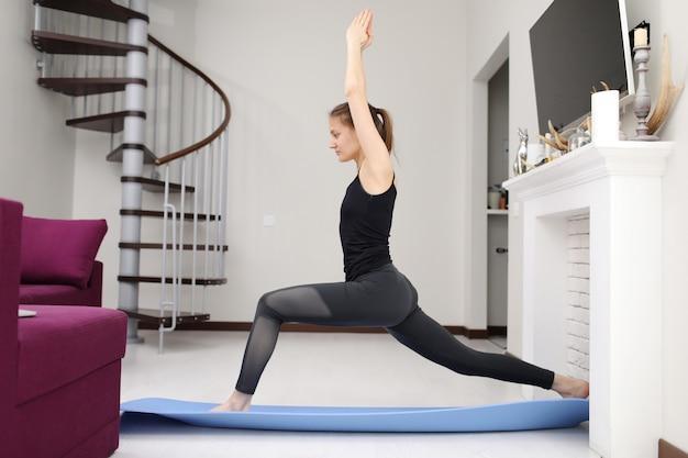 Giovane donna con forma del corpo sottile in abiti sportivi facendo esercizio Foto Premium