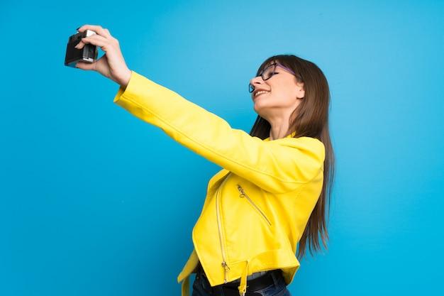 Giovane donna con giacca gialla sul blu in possesso di una macchina fotografica Foto Premium