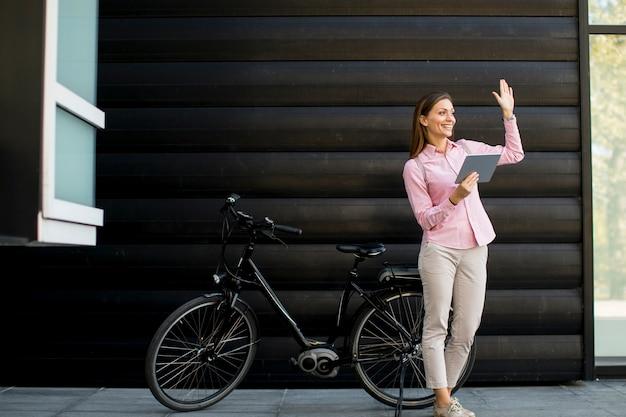 Giovane donna con gli archivi nelle mani che stanno all'aperto accanto alla bici elettrica Foto Premium
