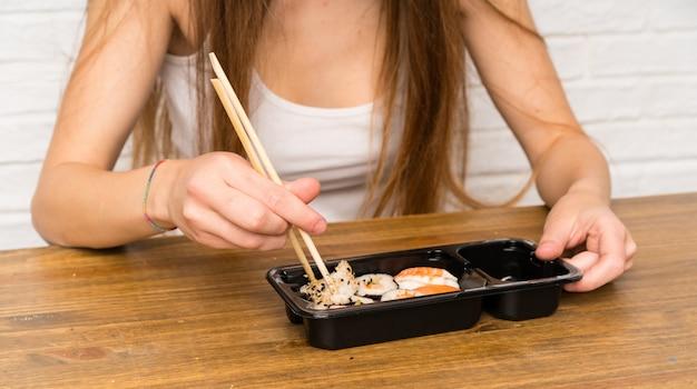 Giovane donna con i capelli lunghi mangiare sushi Foto Premium