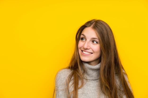 Giovane donna con i capelli lunghi su sfondo giallo ridendo e alzando lo sguardo Foto Premium