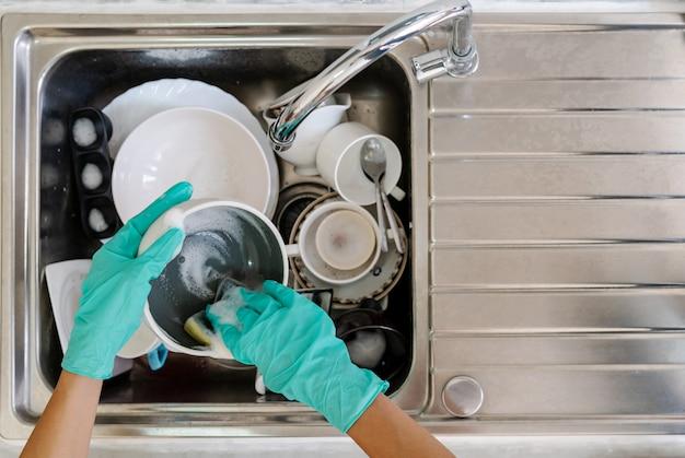 Giovane donna con i guanti lavare i piatti in cucina Foto Premium