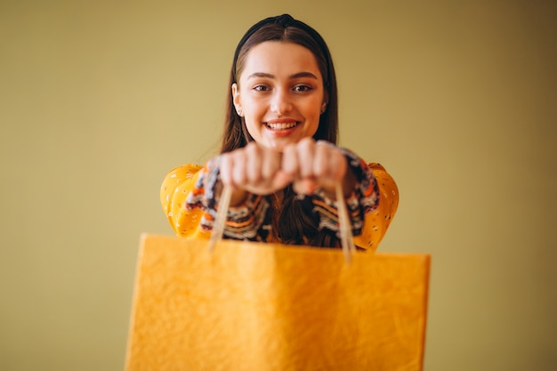 Giovane donna con i sacchetti di shopping in un bel vestito Foto Gratuite