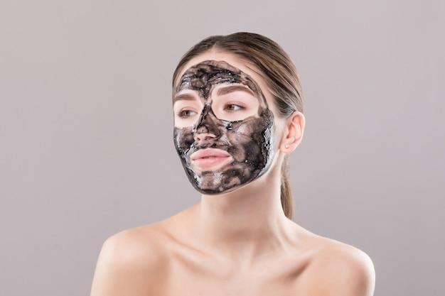 Giovane donna con la maschera nera purificante sul suo fronte isolato sulla parete bianca Foto Gratuite