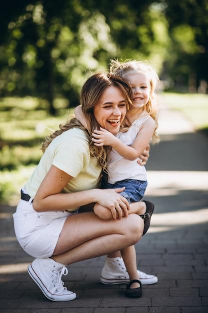 Giovane donna con la piccola figlia che cammina nel parco Foto Gratuite