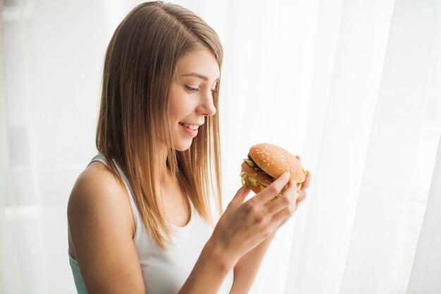 Giovane donna con nastro adesivo sulla bocca, impedendole di mangiare cibo spazzatura, concetto di cibo sano Foto Premium