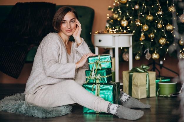 Giovane donna con regalo di natale dall'albero di natale Foto Gratuite