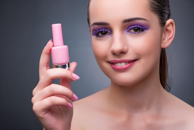 Giovane donna con rossetto nel concetto di bellezza Foto Premium