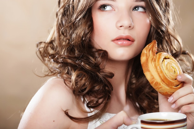 Giovane donna con rotolo di caffè e cannella Foto Premium
