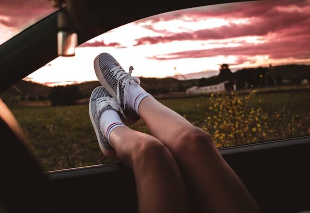 Giovane donna con scarpe da ginnastica con i piedi appoggiati sul finestrino della macchina al tramonto Foto Premium