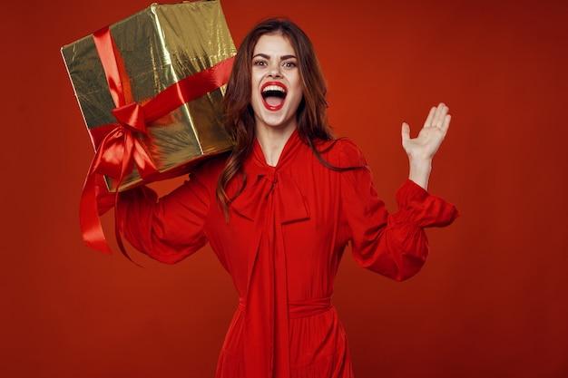 Giovane donna con scatole di regali nelle sue mani in bellissimi abiti, vendita di regali, buon natale e capodanno Foto Premium