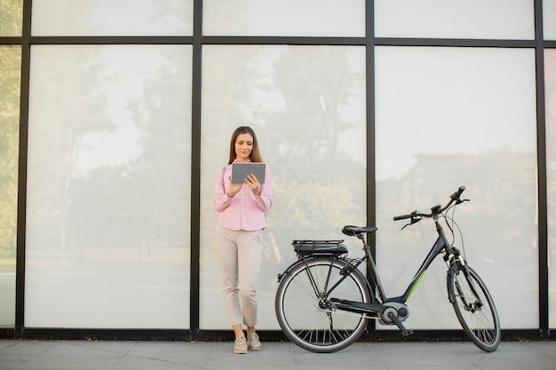 Giovane donna con tablet e e-bike all'aperto Foto Premium