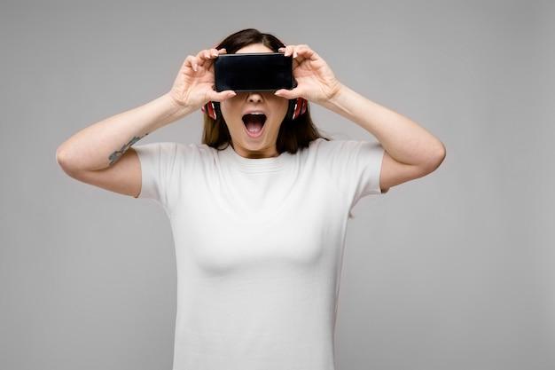 Giovane donna con telefono e auricolari Foto Premium