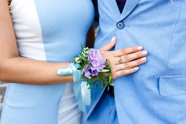 Giovane donna con un fiore all'occhiello floreale su una mano in un vestito blu che abbraccia un uomo in un vestito blu Foto Premium